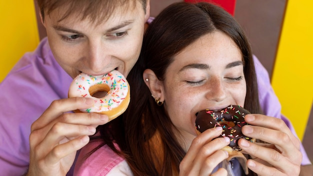 Boyfriend and girlfriend eating donuts outdoors
