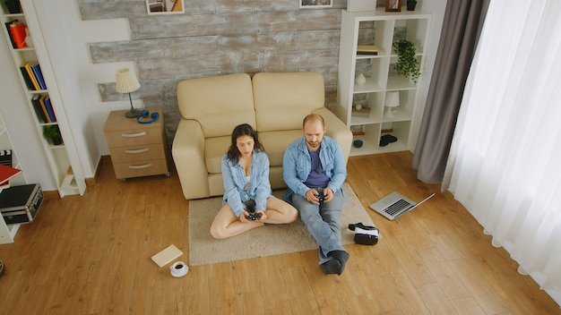 Boyfriend and girlfriend playing video games with wireless controller.