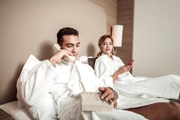 バスローブを着た彼氏。彼の女性の近くに横たわっているルームサービスを呼び出す白いバスローブを着ている黒髪のボーイフレンド
