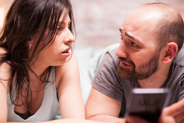 Парень в пижаме обеспокоенно смотрит на свою девушку во время использования смартфона.