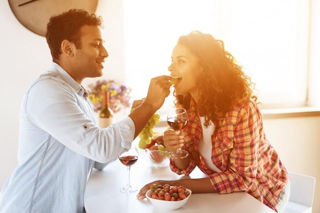Boyfriend is feeding girlfriend with strawberry.