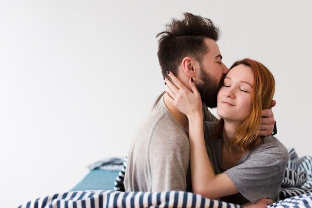 Boyfriend kissing his girlfriend forehead copy space