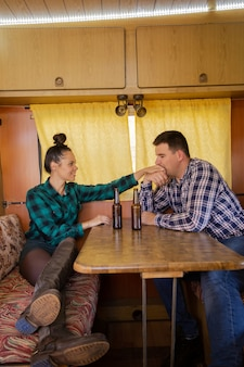Boyfriend kissing his girlfriend's hand is sitting at the table in the retro camper. holiday together