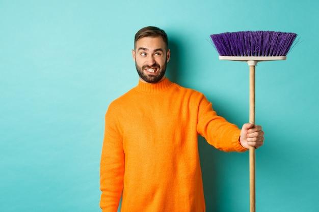 빗자루에 혼란스러워하는 남자 친구, 깨끗한 집, 집안일, 밝은 파란색 배경에 불쾌감을 느낀다.