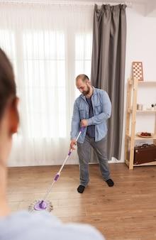 Fidanzato che lava il pavimento in soggiorno