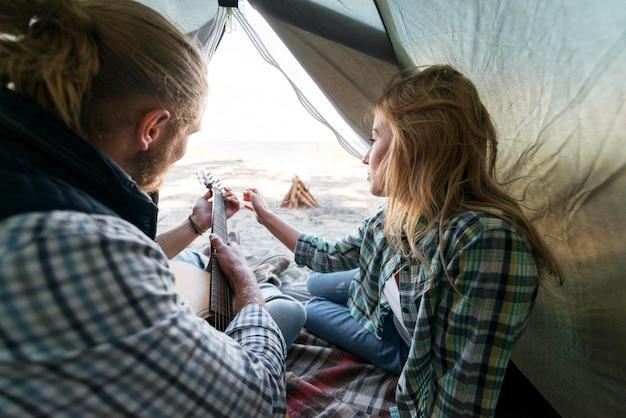 Парень играет на акустической гитаре в палатке, вид сбоку