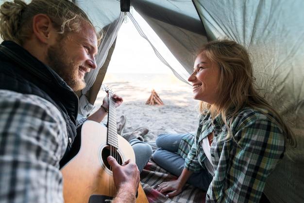 Парень играет на акустической гитаре в палатке