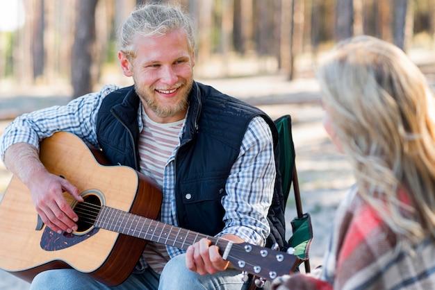 Парень играет на акустической гитаре средний выстрел