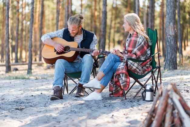 Парень играет на акустической гитаре на открытом воздухе