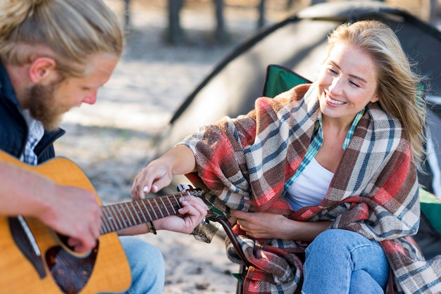 Парень играет на акустической гитаре, вид сбоку