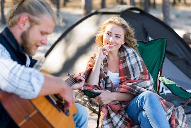Парень играет на акустической гитаре женщина вид спереди