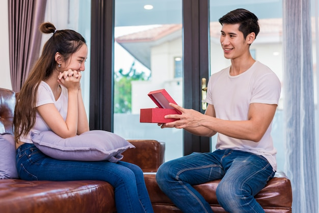 Boyfriend surprising girlfriend with present. woman surprised when looking at gift box on special day