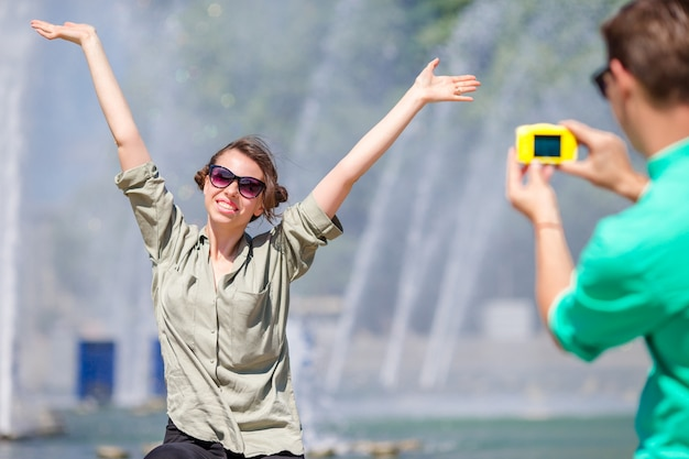 Boyfriend taking a picture of his girlfriend while sitting background the fountain. young man making photo of woman on the street laughing and having fun in summer.