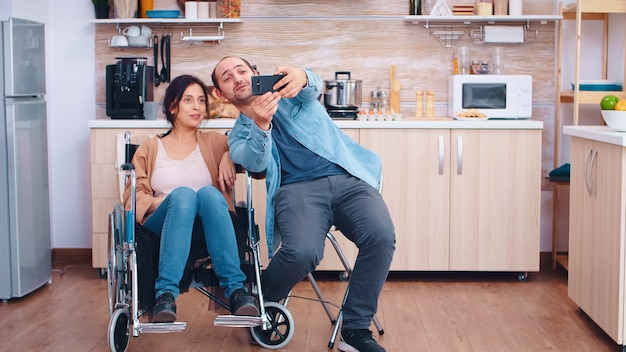 Boyfriend taking selfie with happy and disabled wife in wheelchair. hopeful husband with handicapped disabled disability invalid paralysis handicap person next to him, helping her to reintegrate