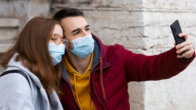 Boyfriend taking selfie with smartphone on him and his girlfriend while wearing masks