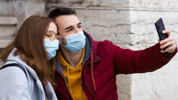 マスクを着用しながら彼と彼のガールフレンドにスマートフォンで自分撮りをしている彼氏