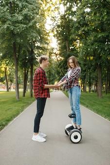 Бойфренд учит свою девушку кататься на гироскопе в летнем парке.