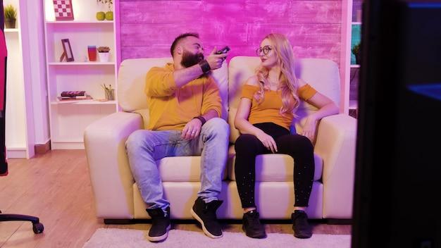 남자 친구는 소파에 앉아 무선 컨트롤러를 사용하여 비디오 게임을 하다가 여자 친구를 이기고 있습니다.