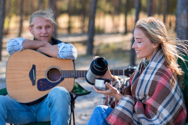 Boyfriend with guitar and girl with coffee