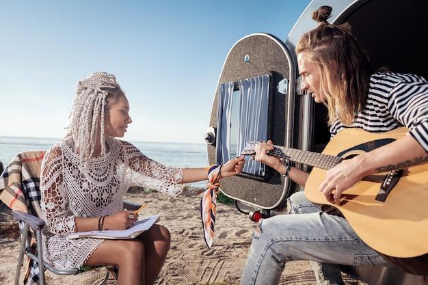 ギターを持つ彼氏。彼女のボーイフレンドのためにギターをチューニングする白いドレッドヘアを持つスタイリッシュな愛情のあるガールフレンド