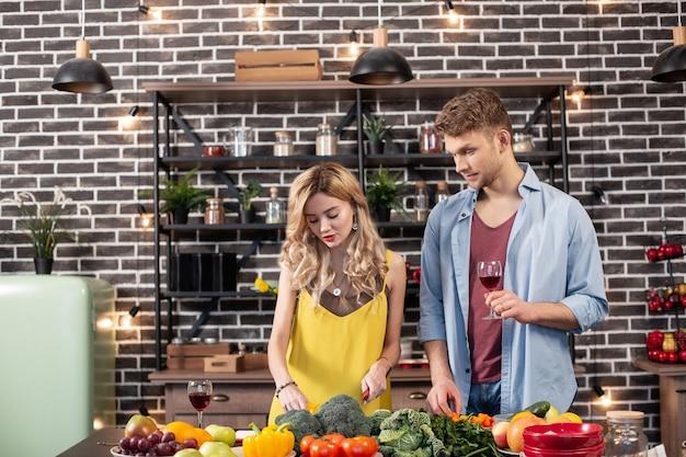 Парень с вином. бородатый красивый парень пьет красное вино, пока его женщина готовит ужин