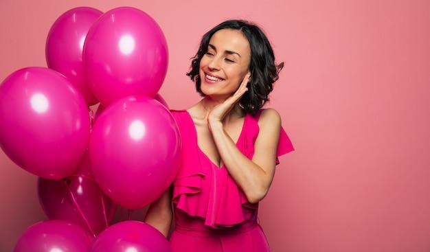Парень присутствует. фотография крупным планом великолепной женщины в розовом платье, которая смотрит на воздушные шары цвета фуксии справа и широко улыбается.