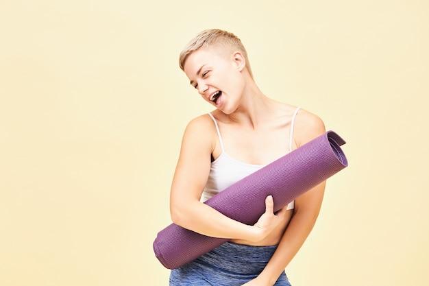Fanciullesca bella ragazza con l'acconciatura da folletto con uno sguardo eccitato felice, cantando o ridendo portando materassino yoga, godendo di uno stile di vita sano attivo sport, fitness, forza, determinazione e motivazione