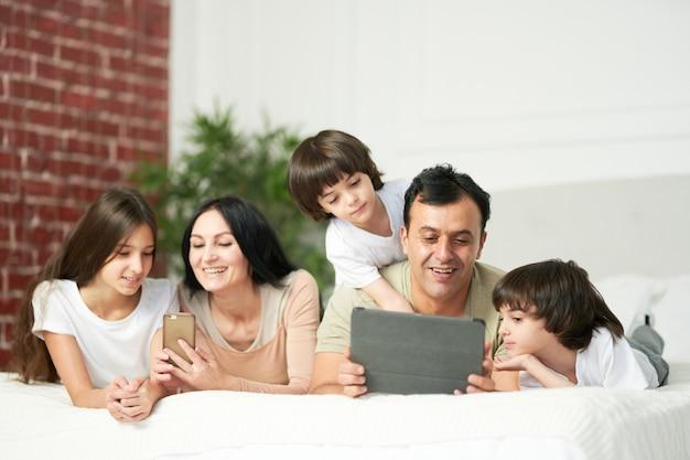 소년과 소녀. 디지털 기기를 사용하는 귀여운 아이들과 함께 침대에 누워 있는 행복한 라틴 가족. 가족, 부모, 기술 개념