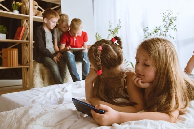 집에서 다른 도구를 사용하는 소년과 소녀. 스마트 시계, 스마트 폰 및 헤드폰을 가진 차일. 셀카 만들기, 채팅, 게임, 비디오보기. 어린이와 현대 기술의 상호 작용.