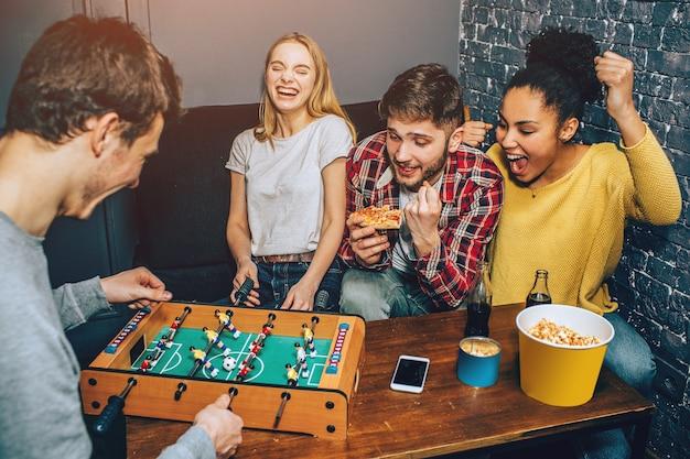 Мальчики играют в настольную игру в футбол на столе, а девочки болеют