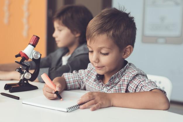 소년들은 집에서 노트북과 현미경을 사용하여 앉아 있습니다.