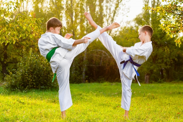 Boys dressed kimono doing karate exercises outdoors