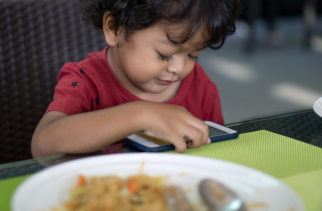 Boys do not eat food because they play smartphones