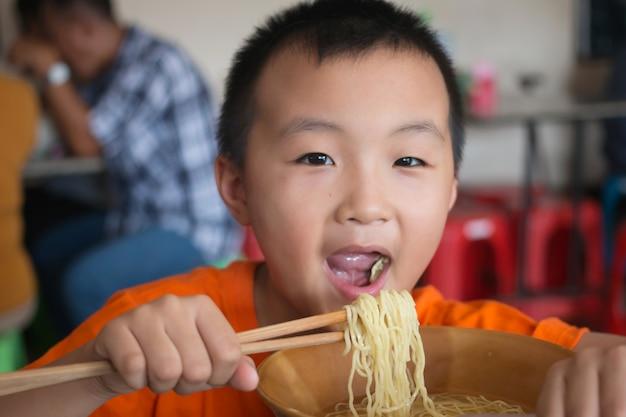 おいしい米ヌードルを食べている男の子
