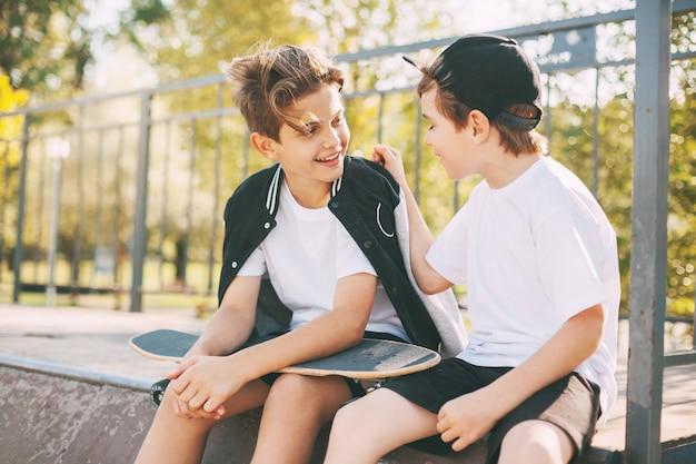 男の子たちはスロープに座ってスケートパークで自由な時間を楽しんでいます。若者の概念