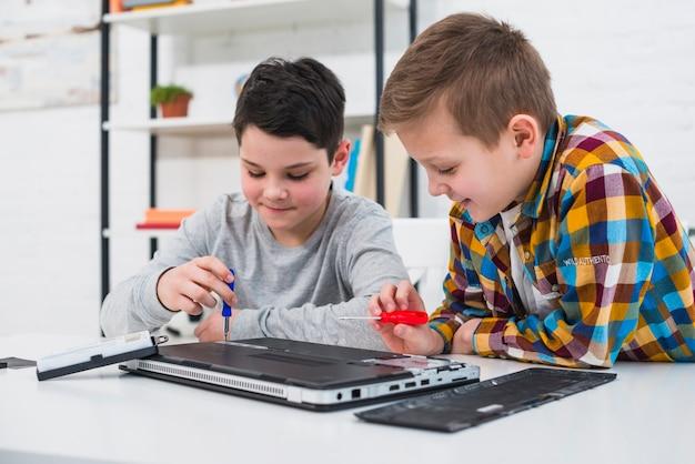 Boys fixing laptop