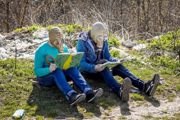 Boys in gas masks in garbage dump read books. environmental pollution
