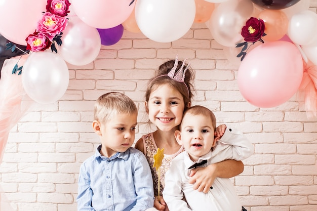 Boys and girl with crowns under birthday balloon and paper flower arch decorations. childish photozone for celebration