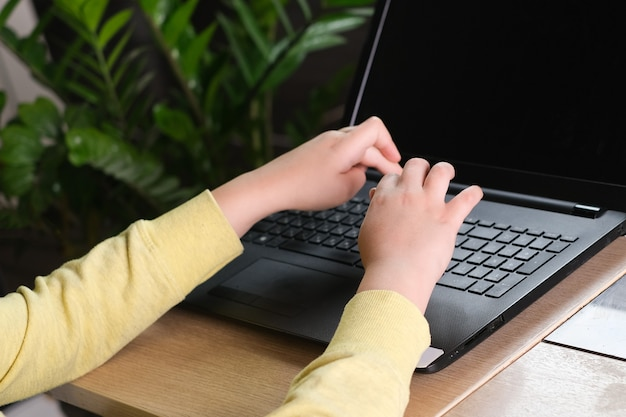 Boys hands in yellow clothes are typing notebook at home background