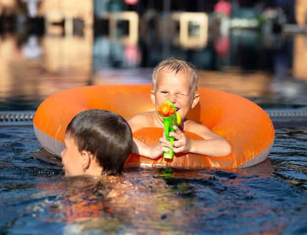 プールフロートと水鉄砲でプールで楽しんでいる男の子