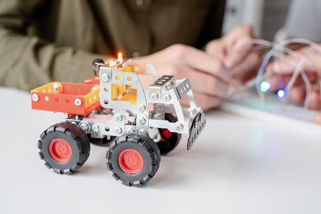 워크숍에서 함께 로봇 자동차를 만드는 재미 소년