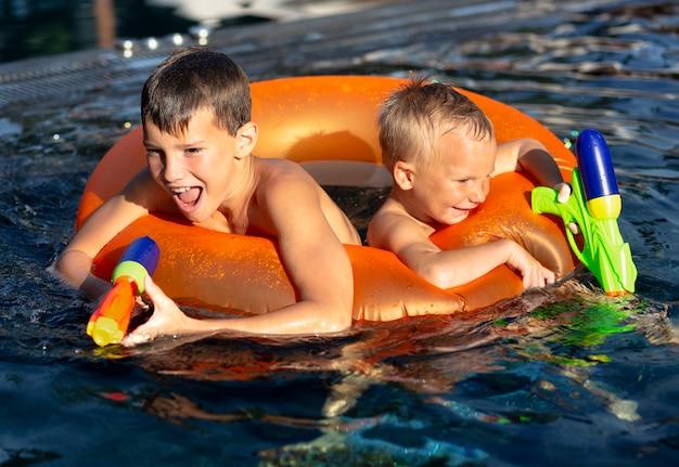 Ragazzi che si divertono in piscina con galleggiante e pistola ad acqua