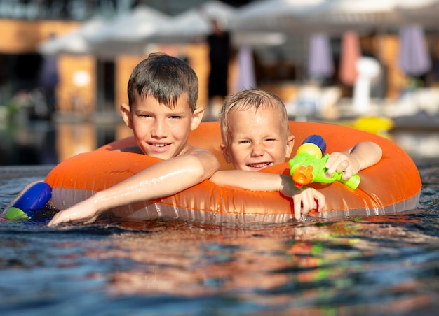 Boys having fun at the swimming pool with pool float and water gun