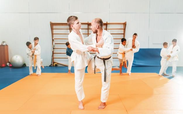 기모노를 입은 소년은 스포츠 체육관에서 무술을 연습합니다.