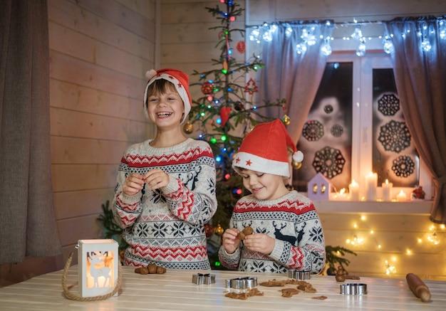 赤い帽子をかぶった男の子がクリスマス休暇のためにジンジャークッキーを準備しています