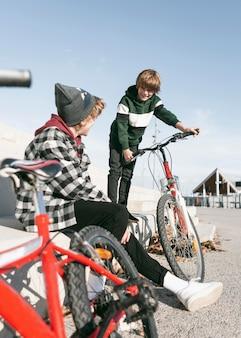 Мальчики в парке веселятся со своими велосипедами