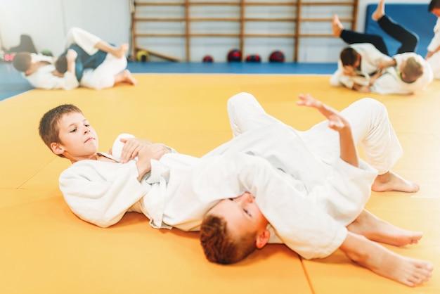 Мальчики в униформе практикуют боевое искусство