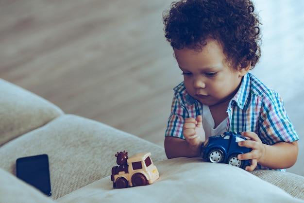 소년들은 작은 기차를 좋아합니다. 집에서 소파 근처에 서 있는 동안 장난감을 가지고 노는 작은 아프리카 아기