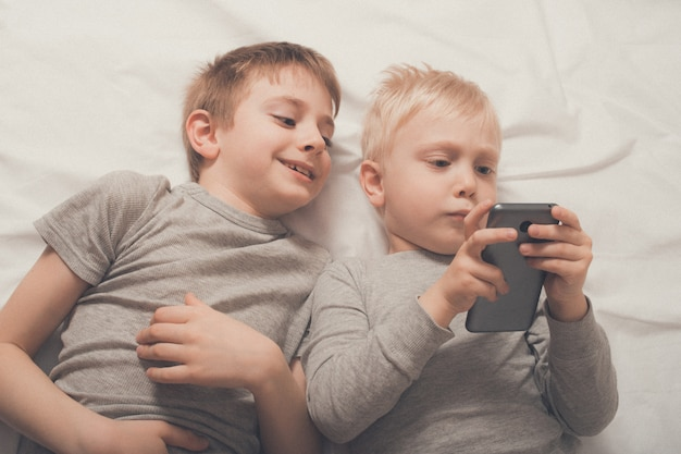 Boys lying in bed with a smartphone