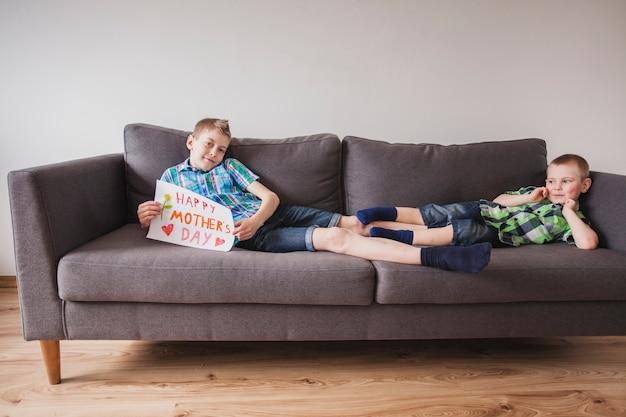 母親の日の看板でソファに横たわっている男の子